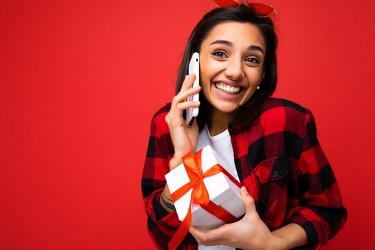 Shot of beautiful happy emotional young brunette woman isolated over red background wall wearing white casual t-shirt and red and black shirt holding white gift box with red ribbon and talking on