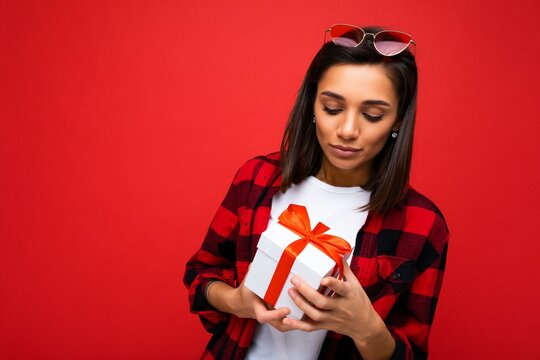 Photo shot of pretty upset sad young brunet woman isolated over colourful background wall wearing trendy outfit look holding gift box and looking at present box with red ribbon
