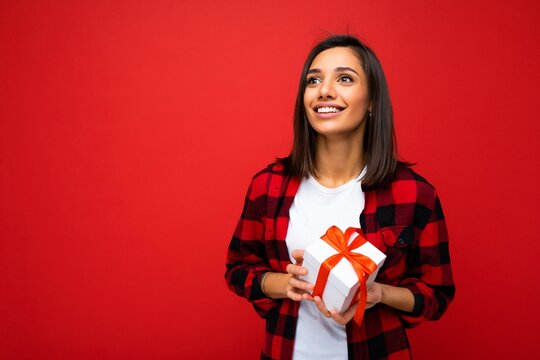 Shot of attractive positive smiling young brunette woman isolated over colourful background wall wearing everyday trendy outfit holding gift box and looking up to the side
