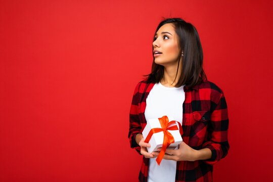 Pretty positive young brunette woman isolated over red background wall wearing white casual t-shirt and red and black shirt holding white gift box with red ribbon and looking to the side and dreaming