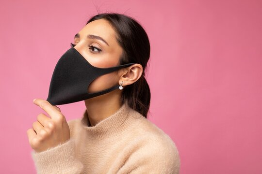 Side-profile shot of young woman wearing an anti virus protection mask to prevent others from corona COVID-19 and SARS cov 2 infection isolated on pink background