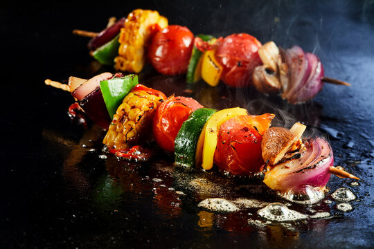Skewers with vegetables on hot cooking surface