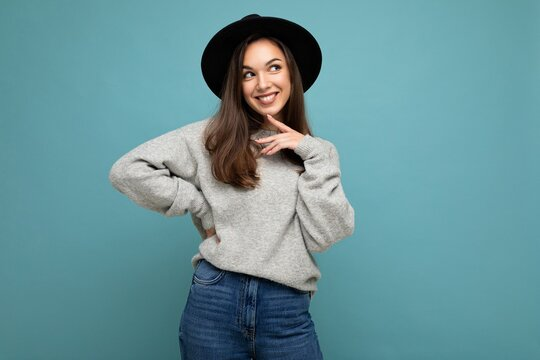 Portrait of young positive happy smiling thoughtful beautiful brunette woman with sincere emotions wearing stylish grey pullover and black hat isolated over blue background with copy space