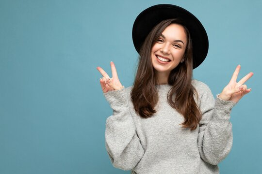 Photo of young positive happy smiling beautiful woman with sincere emotions wearing stylish clothes isolated over background with copy space and showing peace gesture