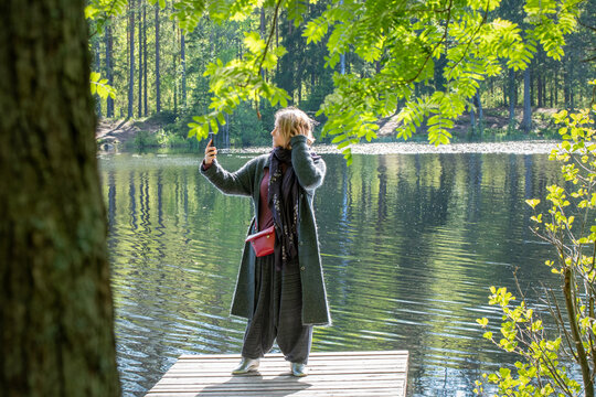 A young woman takes photos of herself with a smartphone on the wooden pier on a forest lake on a sunny summer day.