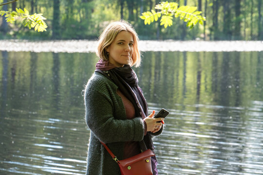 Smiling young woman with a smartphone standing on on the shore of a forest lake on a sunny summer day.