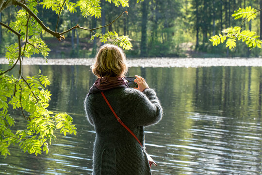Back view of a young woman takes photos with a smartphone on the shore of a forest lake on a sunny summer day.