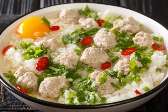 Easy Thai rice soup with meatballs Khao tom moo closeup in the plate on the table. Horizontal