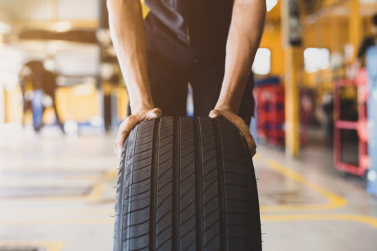 A handsome young mechanic in white gloved uniform is putting his hand on a new tire and checking and checking the condition of the tire while doing car service.