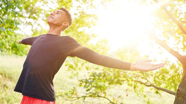 Mann macht Atemübung zur Entspannung in der Natur