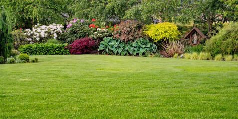 zielony trawnik w pięknym ogrodzie z rabatą kwiatową