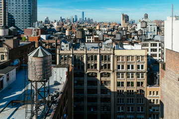 Skyline of Manhattan in New York City with water towers on the rooftops a sunny day with blue sky....