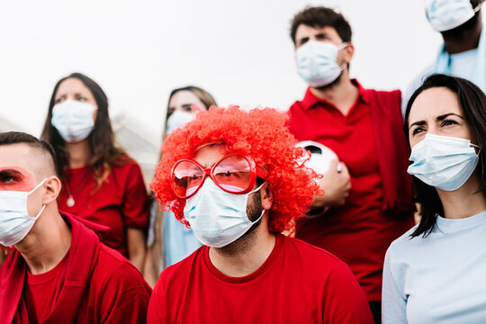 Group of football team supporters in red and blue t-shirt and protective face mask watching concentrated the match from the fan zone at stadium - Live sports new normality concept