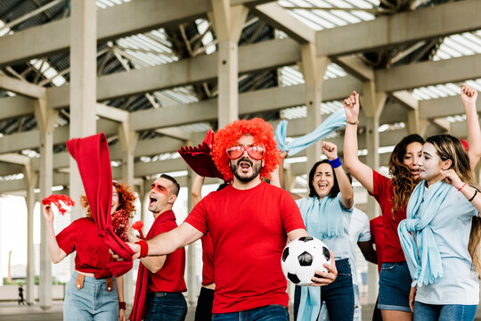 Sport football fans in red and blue t-shirt supporting their team while going to the stadium - Happy multiracial people having fun together outside of stadium