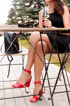 Beautiful woman with long sexy legs having a rest in the street restaurant . Model sitting in an armchair in a cafe.