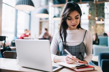 Calm woman writing notes on clipboard - fototapety na wymiar
