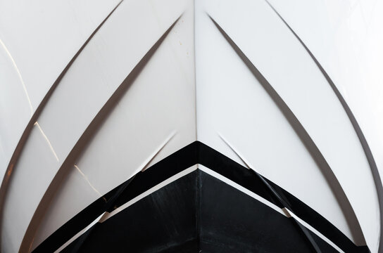 The bow of the yacht, bottom view, close-up. The waterline is clearly visible. Front of a luxury yacht.