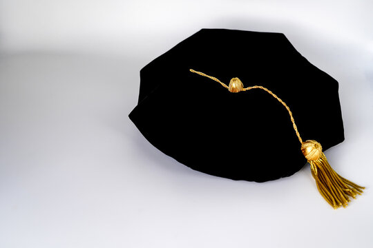 Isolated traditional black phd doctoral tam cap with gold tassel