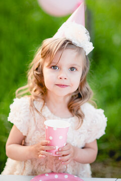 Happy birthday little girl with pink decor in beautiful garden. child eat happy birthday rose cupcake. colorful pastel decoration outdoor. 4 years old kid celebrating enjoying party on summer day.