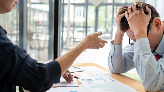 A angry female boss blaming a stressful man about errors on the recent project