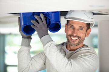 Fototapeta electrician fitting a ventilation system obraz