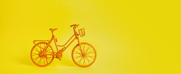 The vintage yellow bicycle parking against yellow wall.