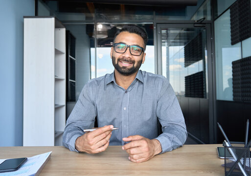 Smiling indian businessman in glasses talking to camera at work by video call conference. Financial advisor executive consulting client remotely online in modern office looking at camera. Webcam view