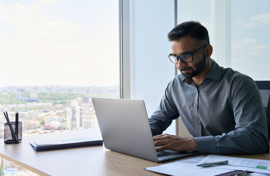 Young indian concentrated ceo sitting at desk using laptop near panoramic window in contemporary corporation office. Serious financial analyst working with big data. Business technologies concept.