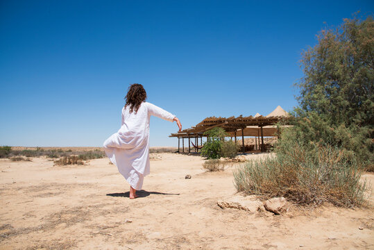 A woman stands in the desert and looks at the horizon. White clothing fluttering in the wind. Concept for relaxation, inner looking, meditation, peace of mind. High quality photo