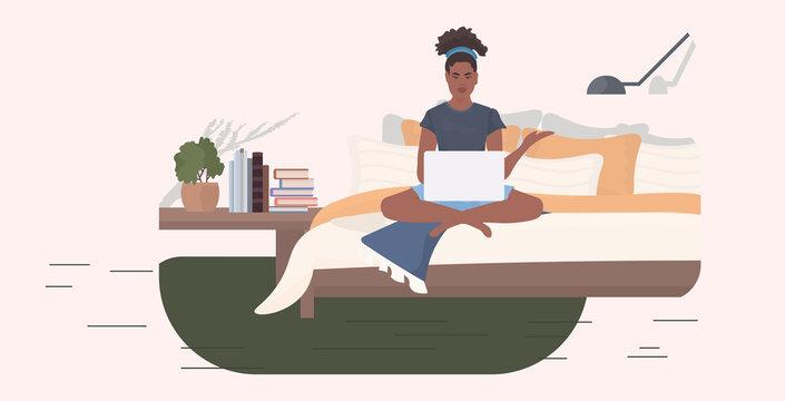 woman freelancer sitting on bed using laptop stay home coronavirus pandemic quarantine concept