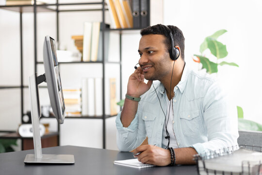 Modern successful Indian businessman in headset is negotiating with multiracial business partners by videoconference using a laptop, Business meeting online concept