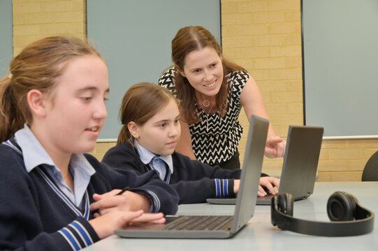 Technology teacher helping how to use laptops in classroom