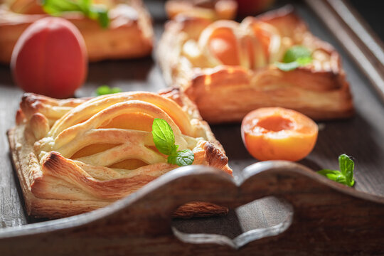 Tasty puff pastry with peaches and mint. Unique yummy cake.