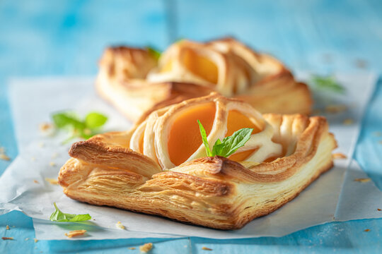 Tasty puff pastry with sugar and peaches. French juicy dessert.