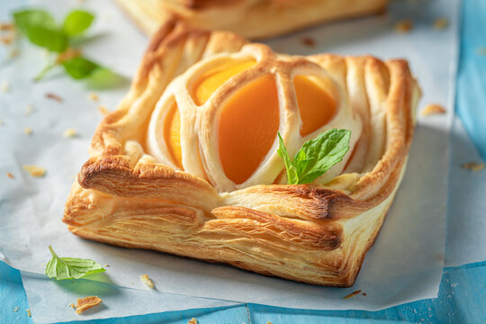 Tasty puff pastry baked with peaches. French juicy dessert.