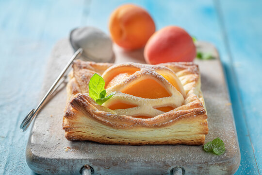 Delicious puff pastry with sugar and peaches. Unique yummy cake.