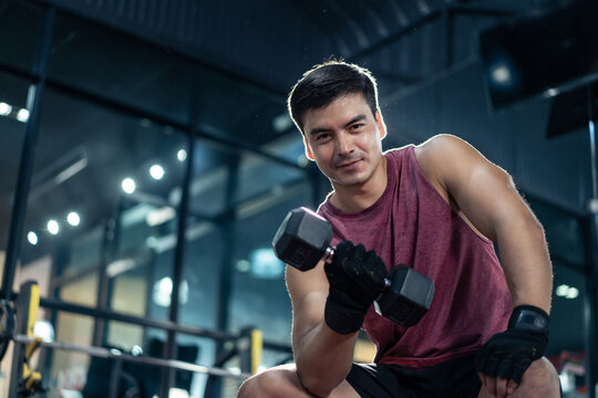 Portrait of Sportsman lift dumbbell and look at camera at fitness gym