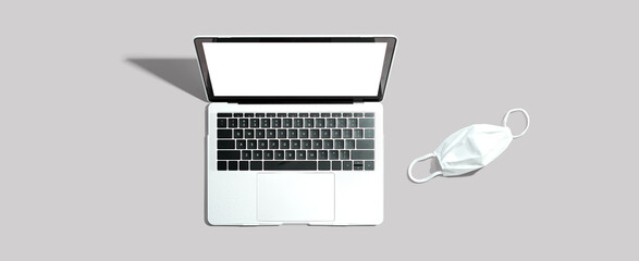 Obraz Laptop computer with a facial mask - fototapety do salonu