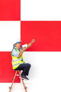 engineer man speak with megaphone on red and white wall constructure building