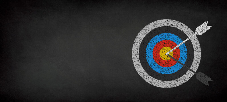 Target with arrow on a chalkboard with copy space