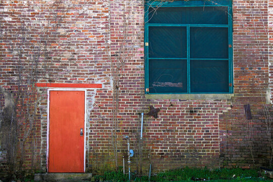 vintage retro old red brick building alley wall with bright red door and green boarded up windows