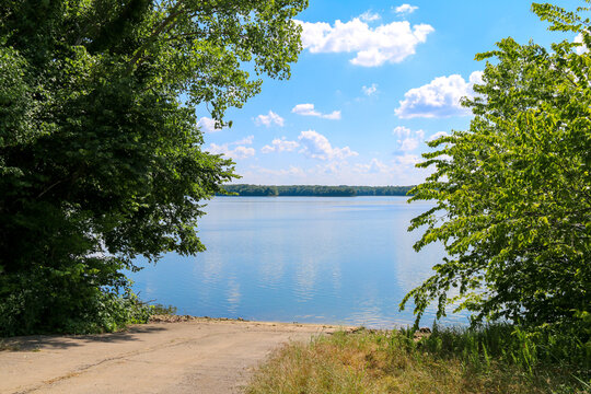 tree lined lake or river dirt fishing boat access ramp with reflections under a bright blue sky and puffy white clouds
