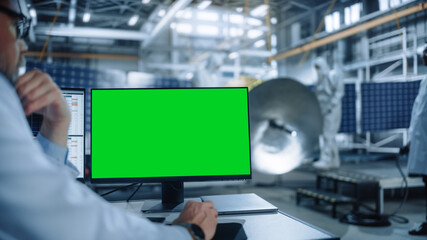 Team of Engineers Working on Satellite Construction. Aerospace Agency International Space Mission: Professional Scientist is Using Computer with Green Screen Mock-up Display. - fototapety na wymiar