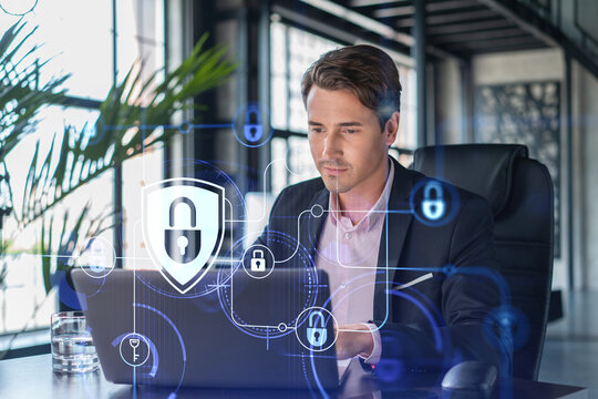 Handsome businessman in suit at workplace working with laptop to defend customer cyber security. Concept of clients information protection and brainstorm. Padlock hologram over office background.