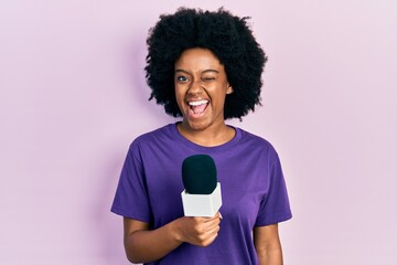 Young african american woman holding reporter microphone winking looking at the camera with sexy...