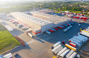 Fototapeta Logistics park with warehouse and outside storage of wooden pallets. Semi-trailers trucks standing on car parking and waiting for loading and unloading goods at ramps. Aerial view obraz