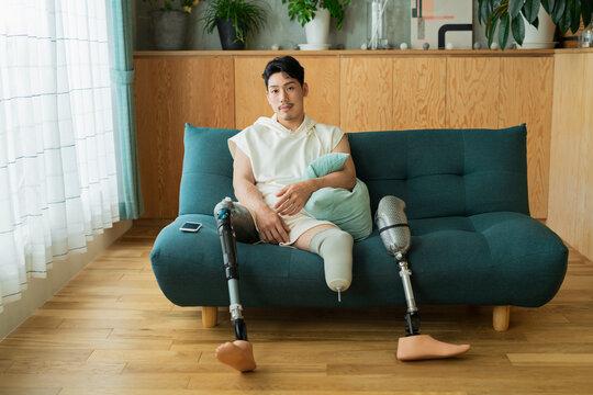 ソファでくつろぐ義足の男性