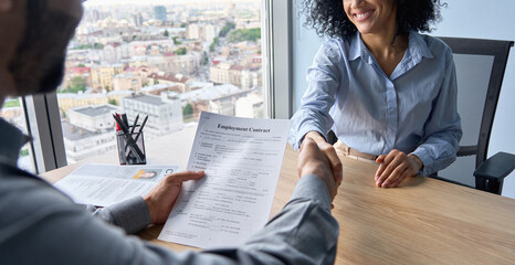 Fototapeta Closeup of Indian latin ceo holding employment contract job offer hiring welcoming female African American newcomer worker manager shaking hands in contemporary office. Human resources concept. obraz