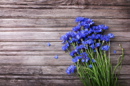 Bunch of blue cornflowers on rustic wooden board top view.