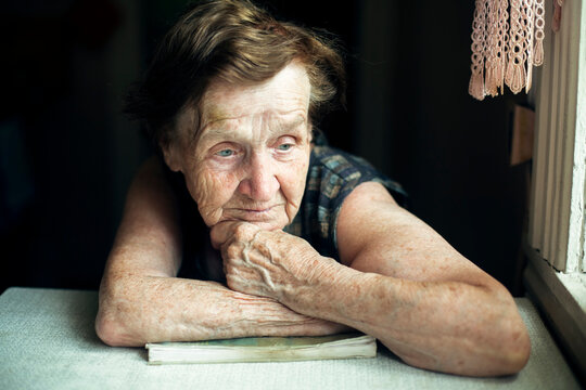 An elderly woman sits thoughtfully in her house.